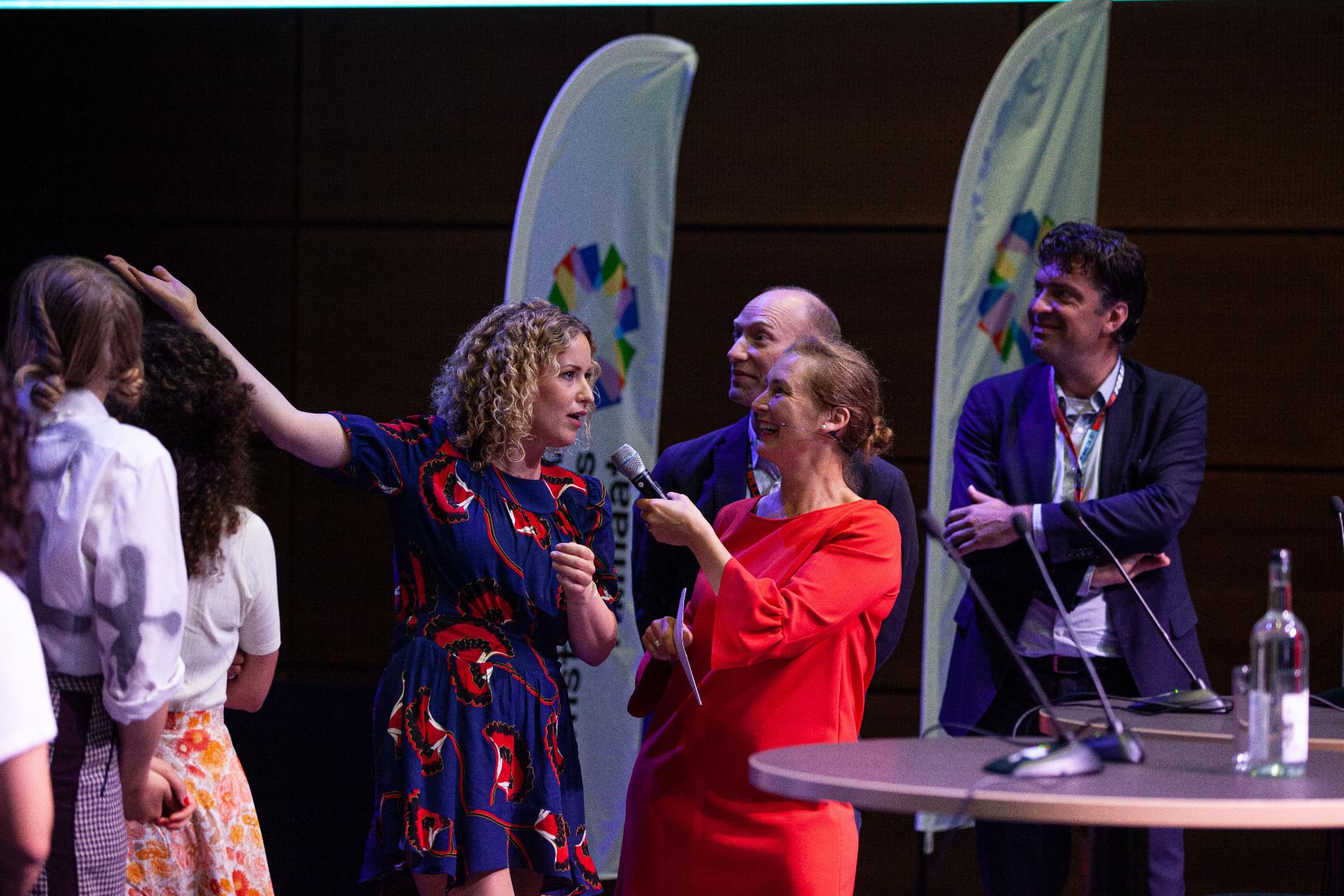 Dagvoorzitter Natasja van den Berg op het podium in gesprek met initiatiefnemers Klimaatakkoord