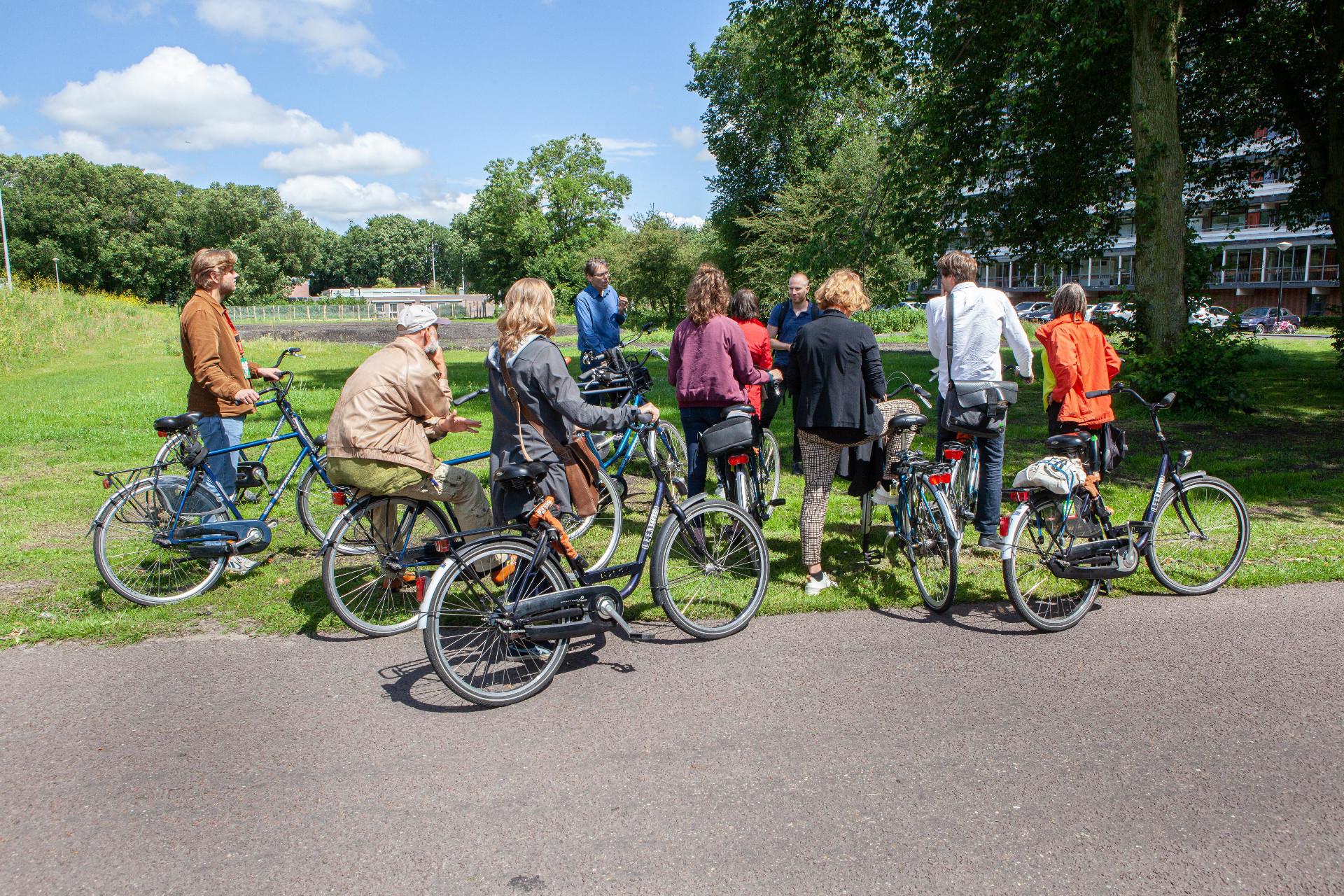 Deelnemers Klimaatakkoord op de fiets voor een route langs duurzame energie-initiatieven in Amsterdam