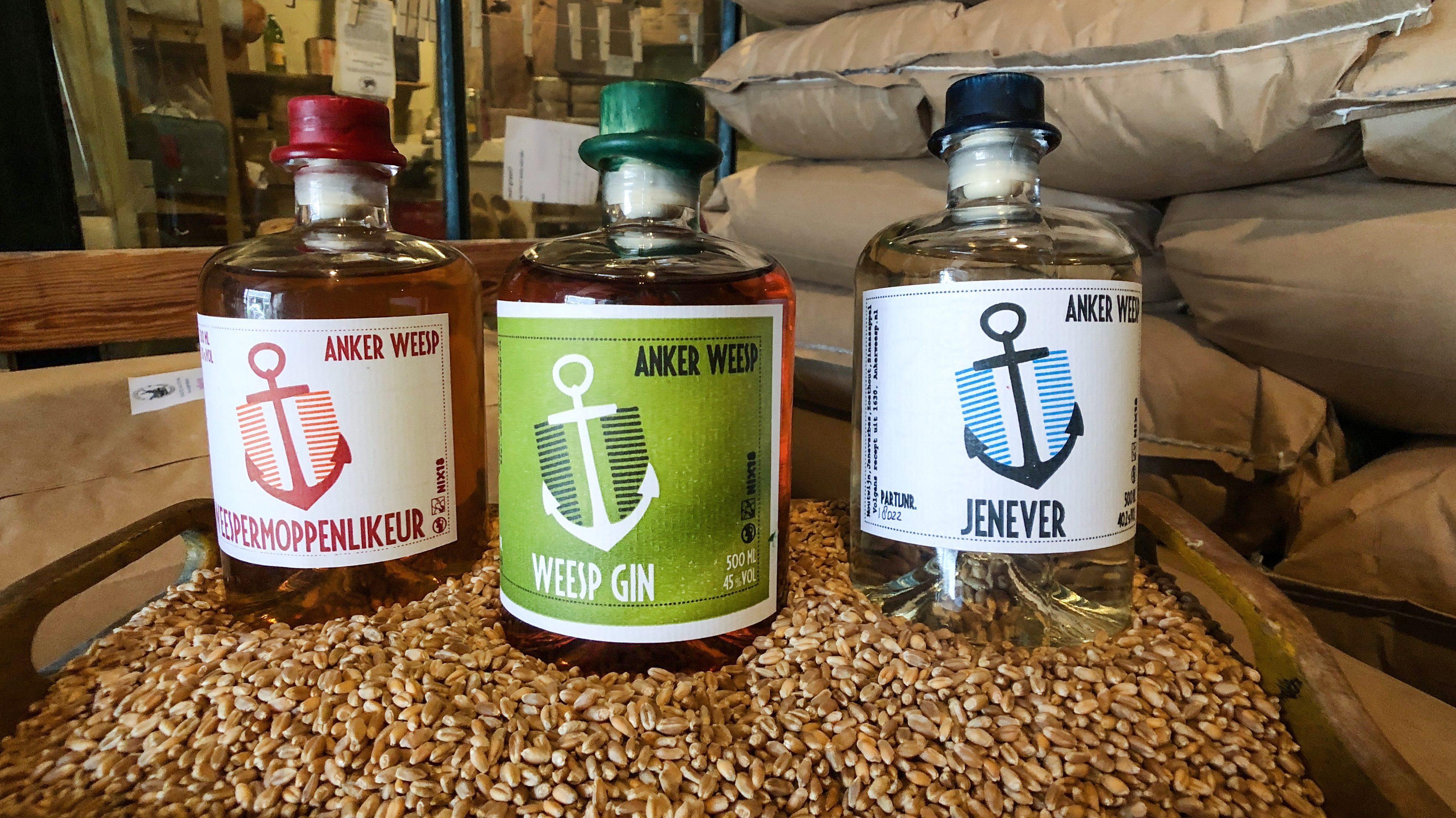 Productfoto met drie flessen met etiket waarop een anker als logo staat: Weespermoppenlikeur, Weesp gin en Jenever
