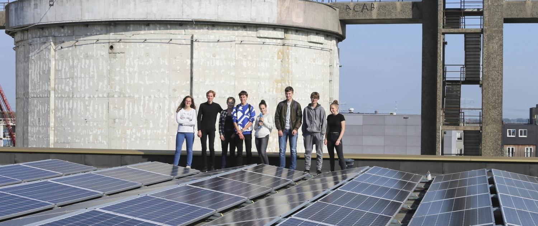 Leerlingen tussen zonnepanelen op dak van IJburgcollege