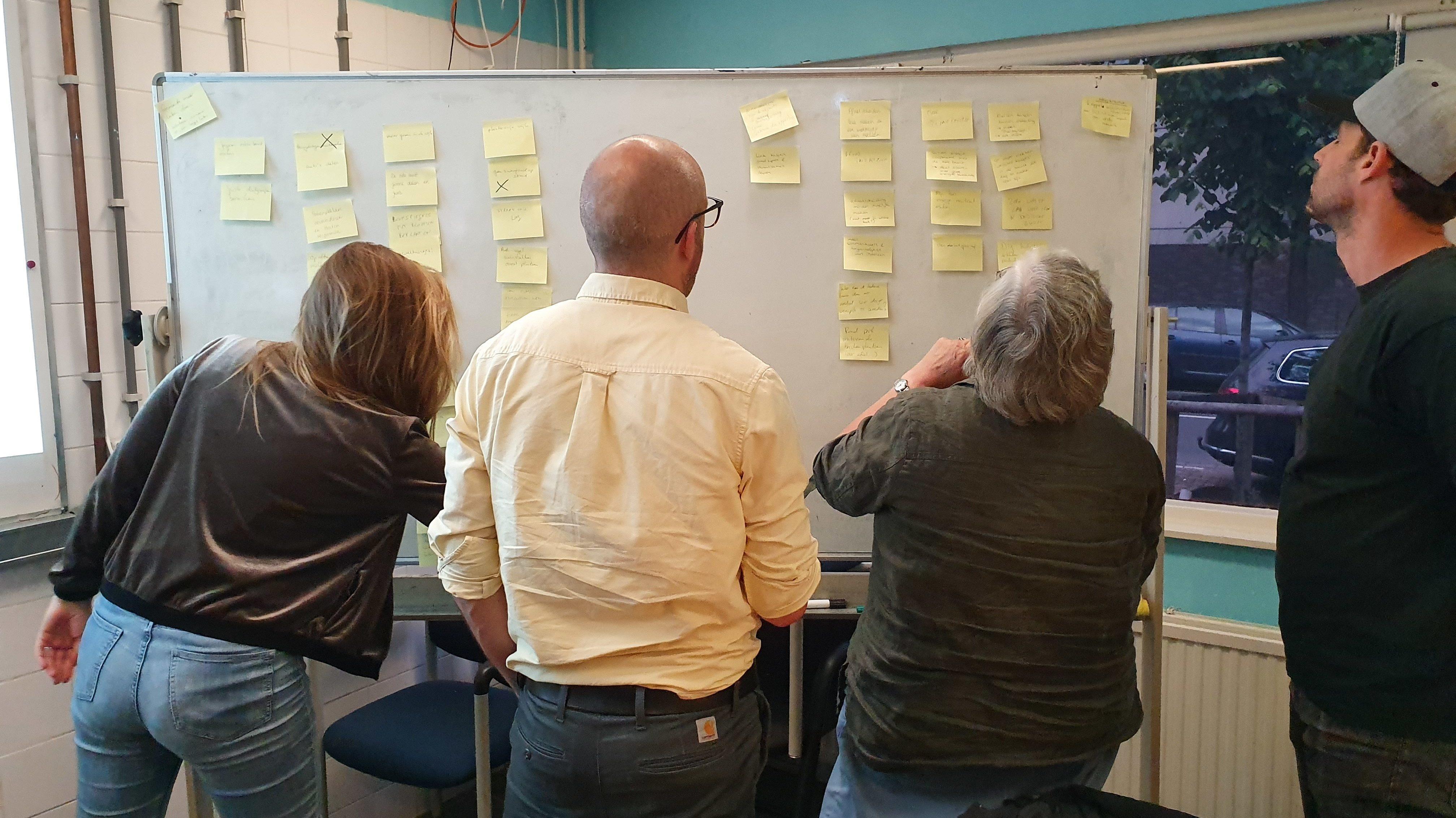 Deelnemers bij whitboard met post-its tijdens brainstormsessie Samen Vooruit. Foto Samen Vooruit