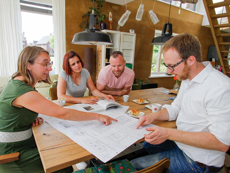Deelnemers Duurzame Huizen Route aan tafel bekijken bouwtekeningen