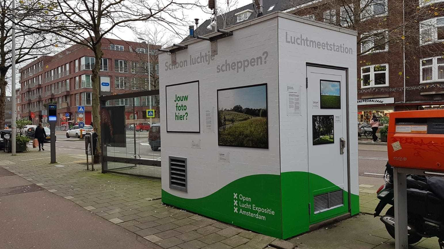 Witte kleine container met deur. Beplakt met landschapfoto's voor Open Lucht Expositie en tekst 'Schoon Luchtje Scheppen?'