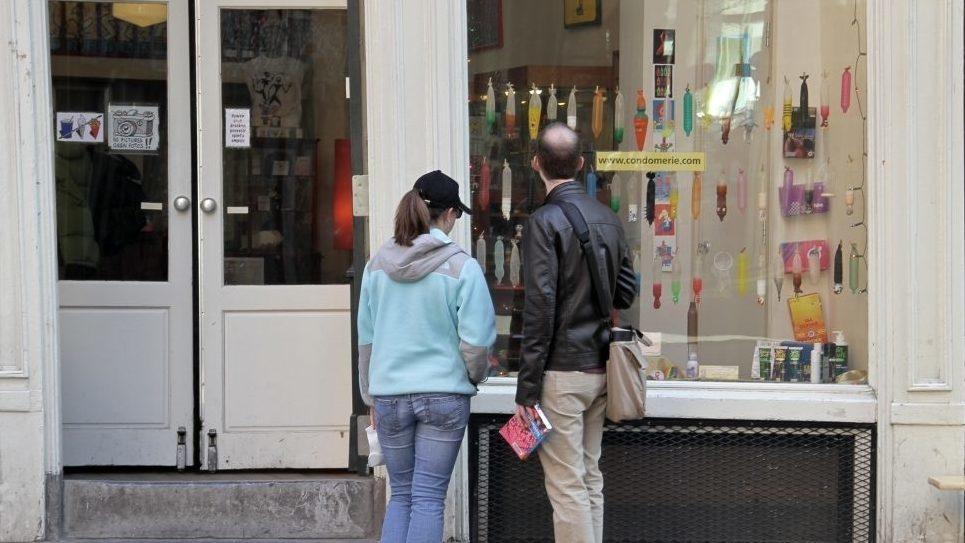 Twee mensen voor de etalage van de Condomerie bekijken condooms