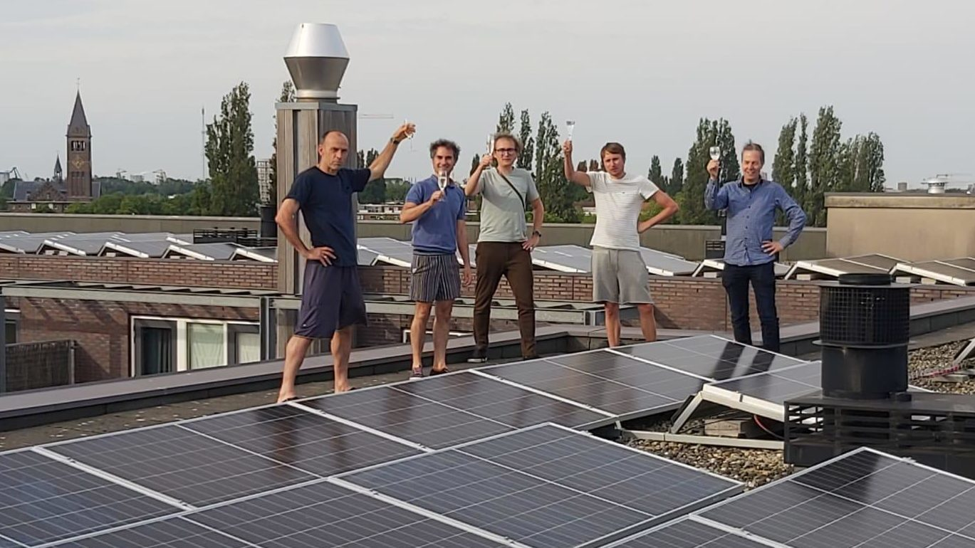 5 mannen staan op een dak tussen zonnepanelen en toosten met een glas champagne