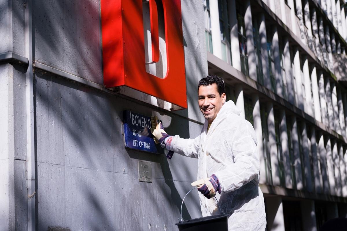 Man poest straatbordje op gebouw van gemeentelijk monument Plan van Gool