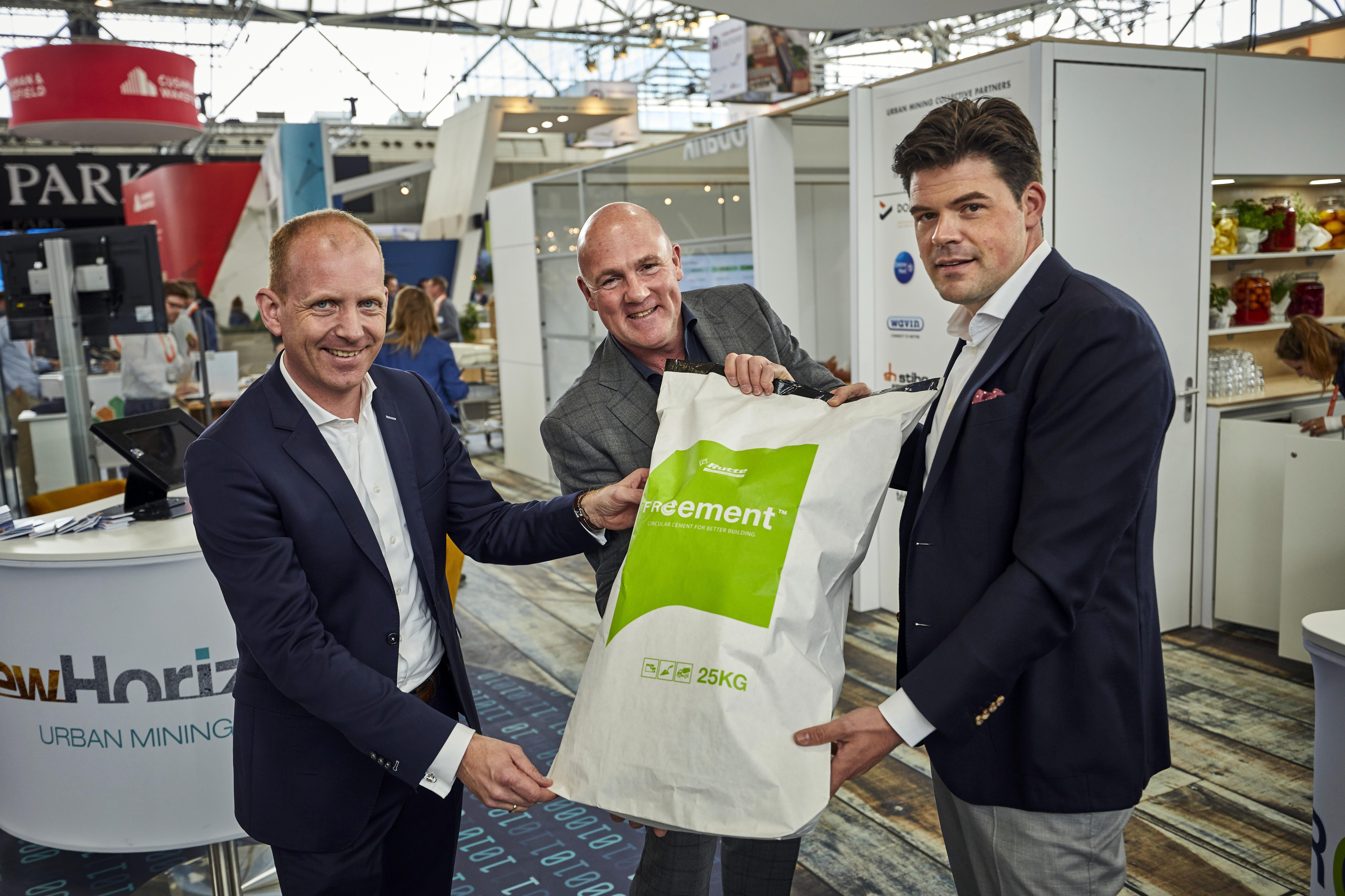 3 mannen presenteren zak met circulair cement gemaakt met Smart Liberator project