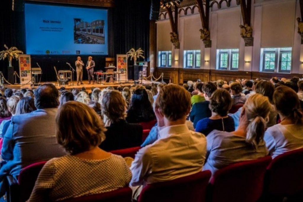 Publiek luistert naar lezing over Duurzame Ontwikkelingsdoelen (SDG) door SDG House