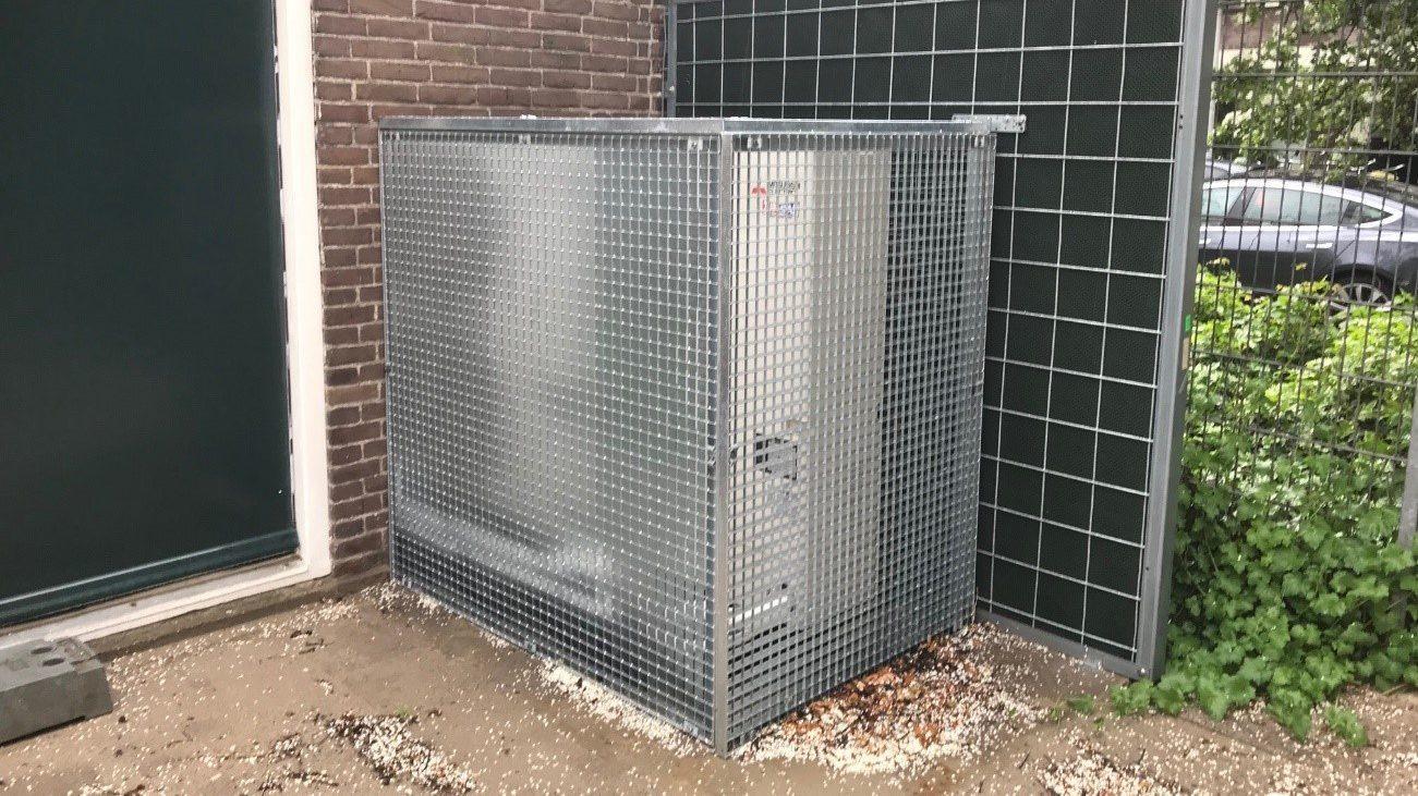 Warmtepomp in stalen kooi naast een deur