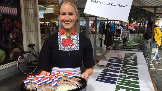 Meisje in klederdracht biedt haring aan bij informatiekraam Watergraafsmeer Samen Duurzaam