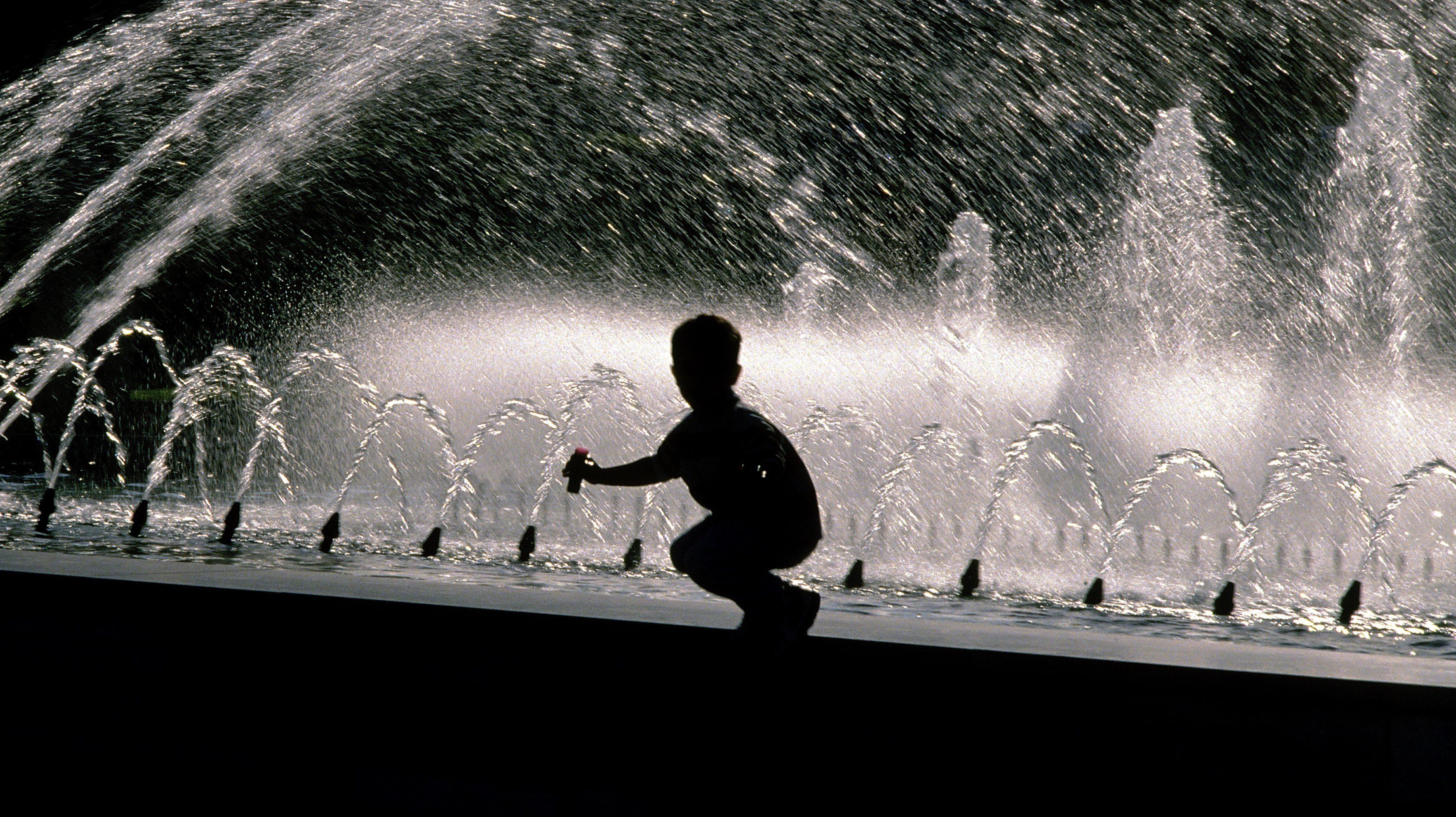 Kindje speelt met water bij fontein