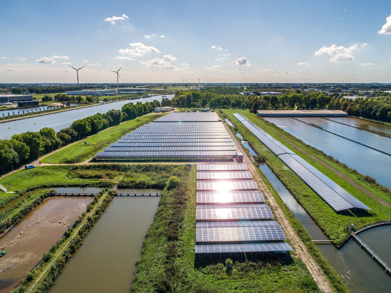 Zonnepanelen in landschap tussen groen en water