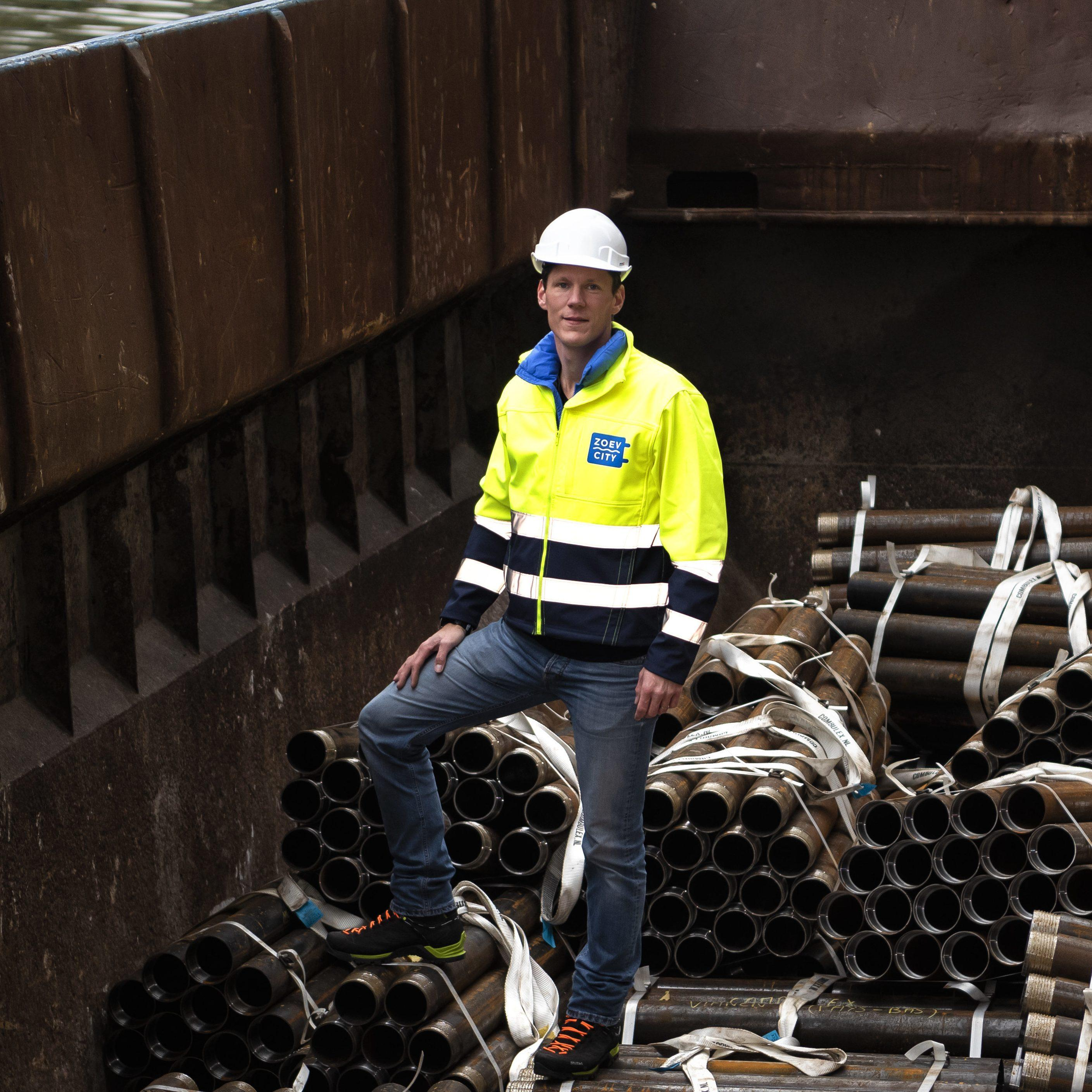 Medewerker tussen bouwmaterialen op elektrische sleep- en duwboot van Zoev City