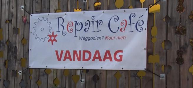 Wit promotiespandoek Repair Café met rode en blauwe tekst: Weggooien? Mooi niet!