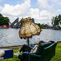 Zittende mensen op bank naast oude lamp buiten aan water