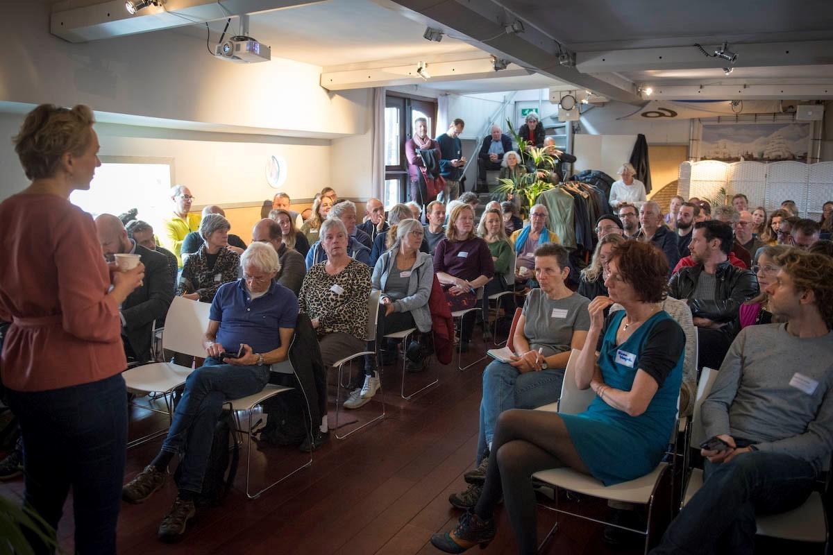 Deelenmers van de Duurzame Woonboten Route zitten in zaal te luisteren naar spreker