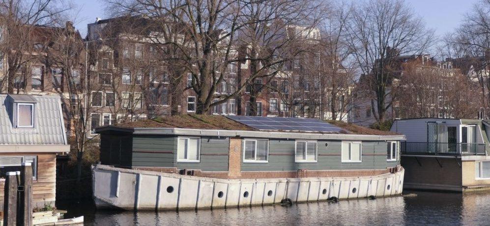 Woonschip met zonnepanelen en een groen dak in Amsterdamse wateren