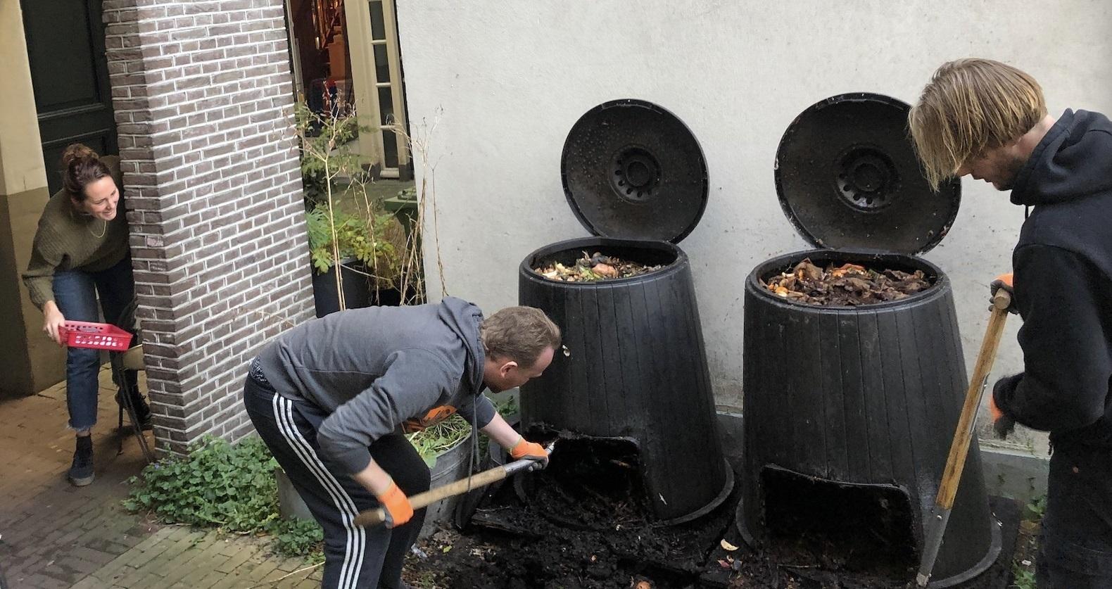 Twee mensen scheppen compost uit twee compostbakken.