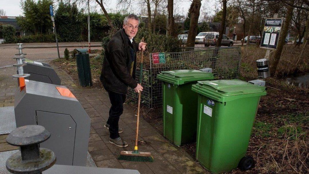 Addie Weenk met bezem in de hand tussen vuilcontainers en groene compostbakken.