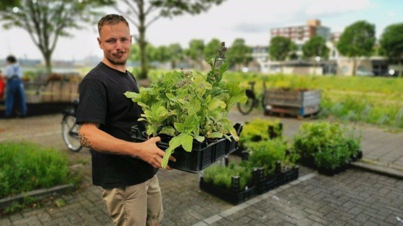Deelnemer NK Tegelwippen met planten in de hand op een parkeerplaats