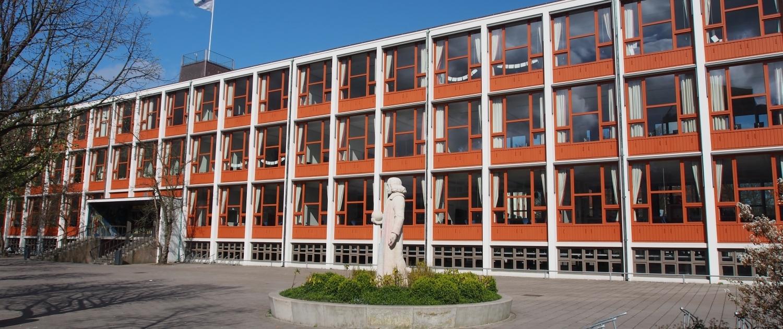 Voorkant schoolgebouw Spinoza Lyceum met veel raampartijen in rode kozijnen. Op het schoolplein staat een standbeeld van Spinoza.