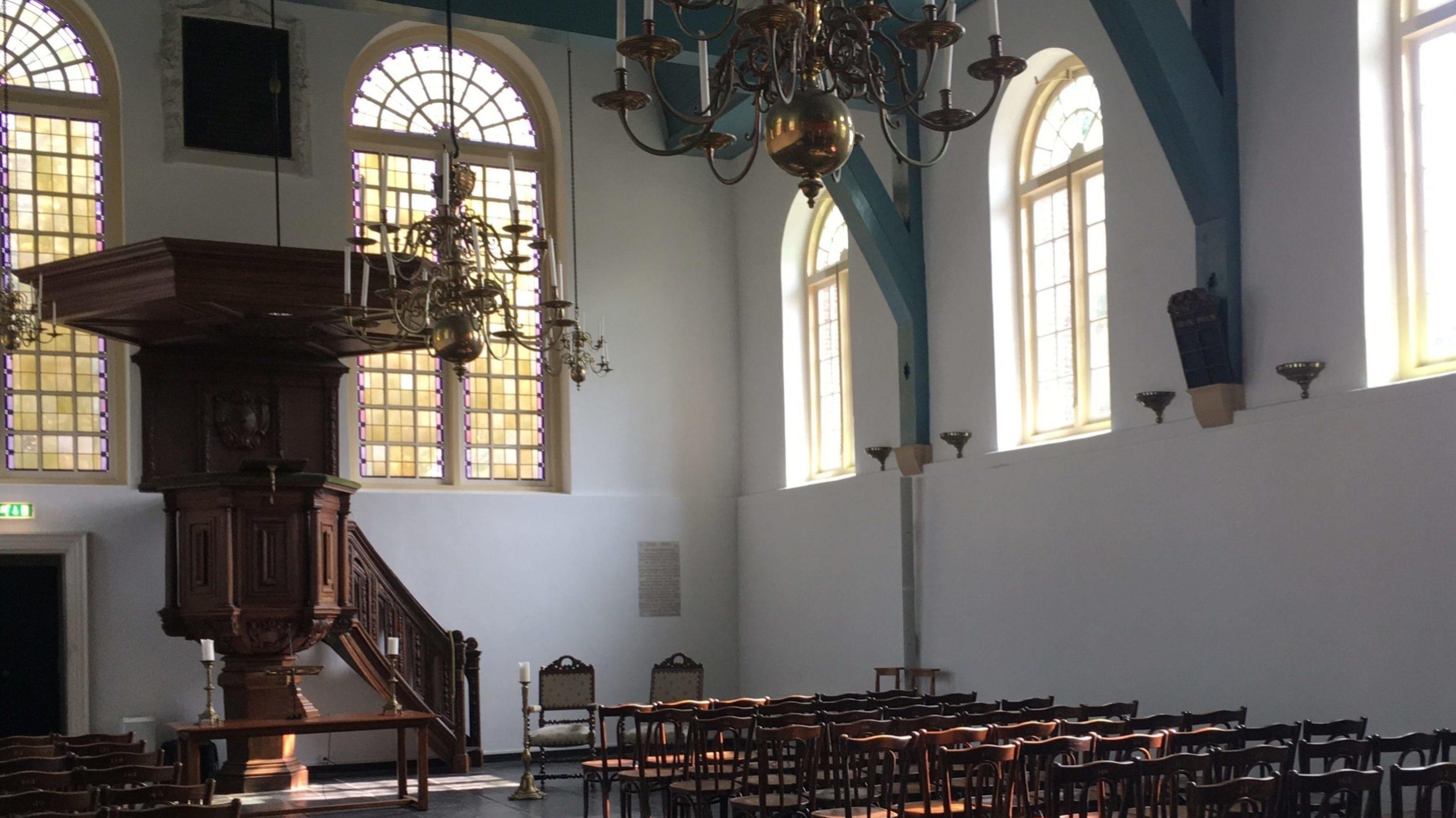 Interieur Petrus kerk met verhoogde houten preekstoel, rijen houten stoelen en kroonluchters.