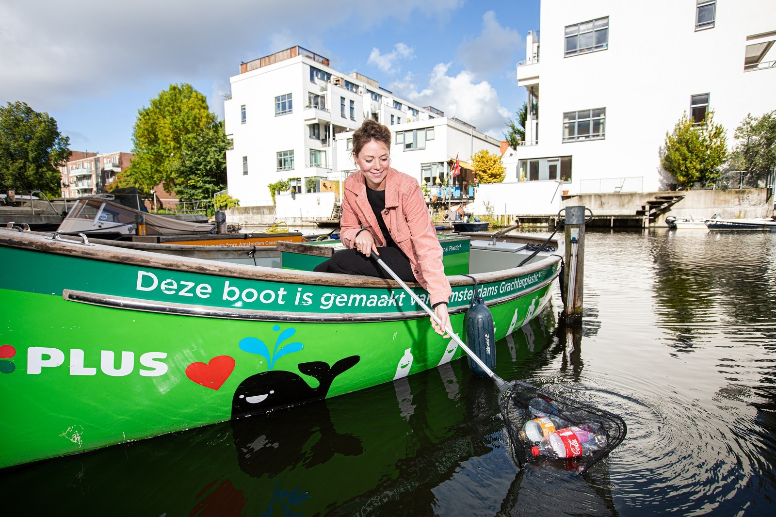 Portret Jutta die plastic uit het water vist met schepnet op een boot in de Amsterdamse grachten