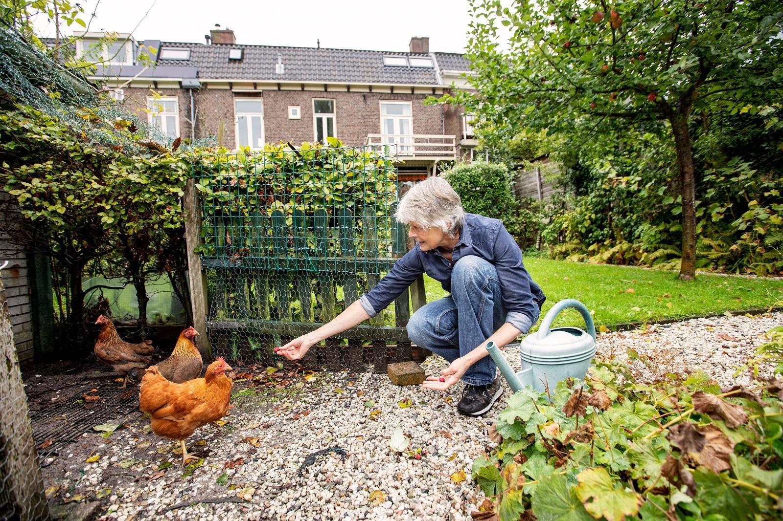 Portret Chris die kippen voert in haar tuin. Foto uit Routekaart Amsterdam Klimaatneutraal