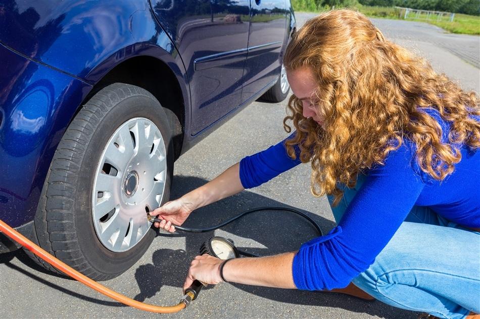 Vrouw vult autoband met lucht