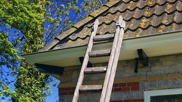 Ladder staat tegen dakgoot geplaatst